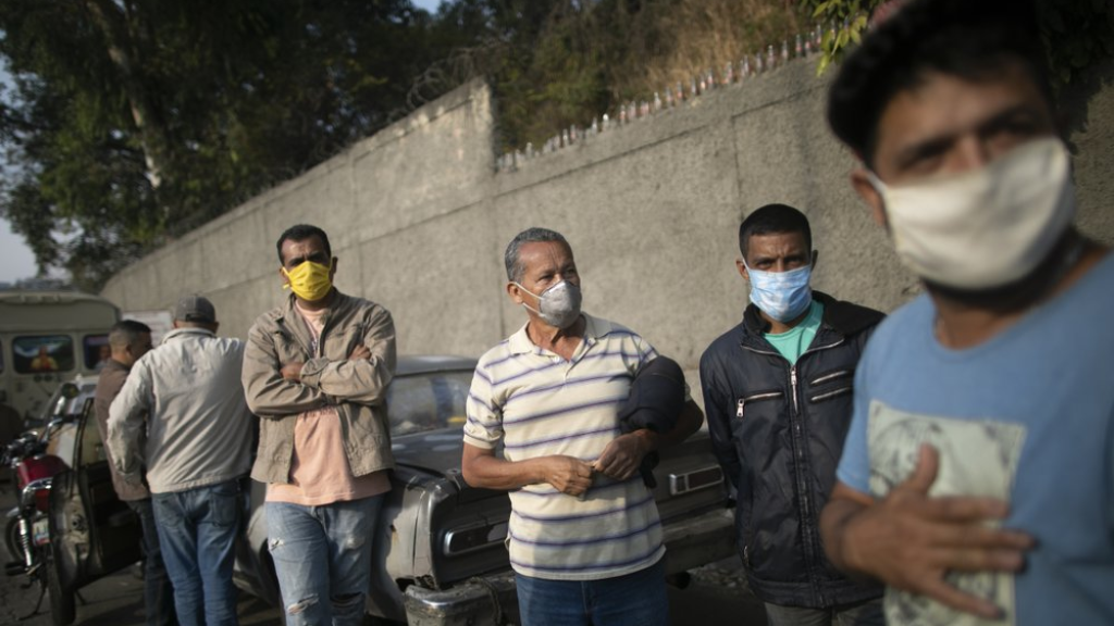 Men stand close to their cars as they wait for hours to fill their cars up with gasoline in Caracas, Venezuela, Thursday, April 02, 2020. Lines at gas stations around the country's capital are getting longer and longer with some saying it was only this bad during the oil worker's strike of 2002. (AP Photo/Ariana Cubillos)