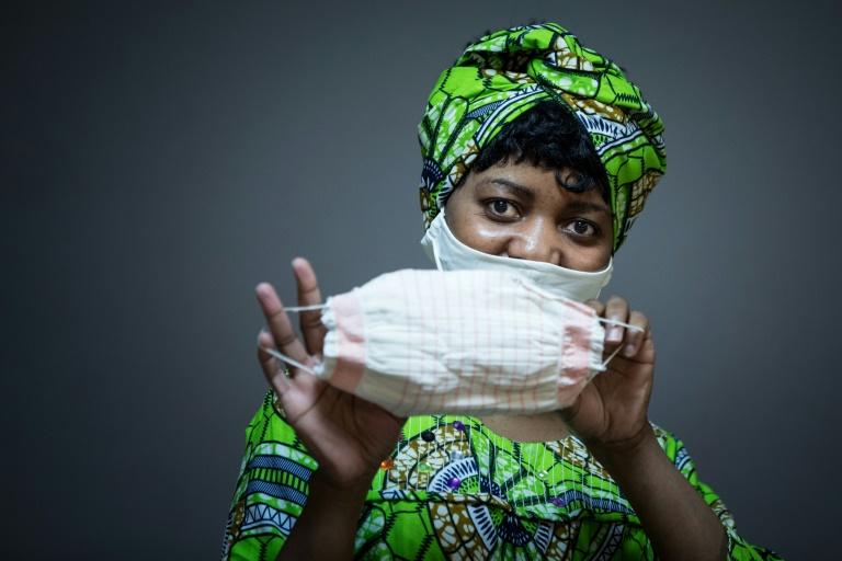 La camerounaise Florence pose avec un masque qu'elle a réalisé pour l'organisation caritative de l'Armée du Salut, à Paris le 6 avril 2020