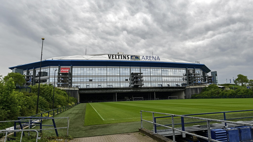Rain clouds draw over the stadium Veltins Arena and the rolled out pitch of Bundesliga club FC Schalke 04 in Gelsenkirchen, Germany, Wednesday, April 29, 2020.  (AP Photo/Martin Meissner).