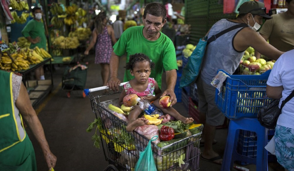 In this March 18, 2020 photo, Cesar Alegre, accompanied by his 4-year-old daughter Lia, places a damaged apple in his shopping cart filled with discarded produce given to him by vendors at a popular market in Lima, Peru. A month-long quarantine to curb the spread of the new coronavirus has forced millions of Peruvians to stay home and closed restaurants and food kitchens making it harder to feed his children. (AP Photo/Rodrigo Abd)