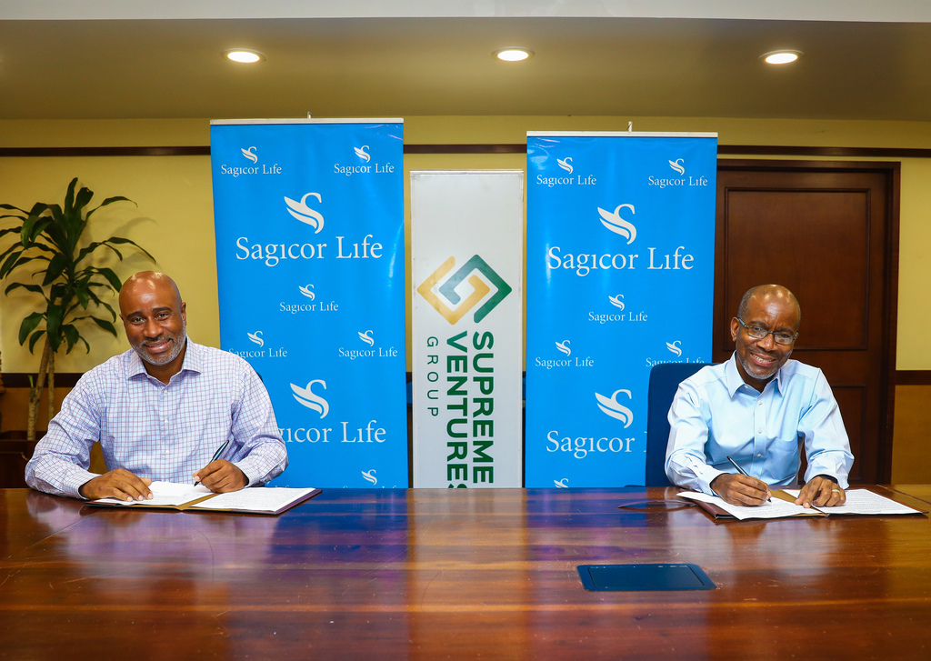 CEO of Prime Sports (Jamaica) Limited, Xesus Johnston (left) and Sagicor Executive Vice President, Life Jamaica Employee Benefit, Willard Brown (right) sign the agreement to provide health coverage to Supreme Ventures retailers at the Sagicor Life headquarters in New Kingston.