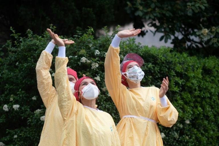 Des soignants saluent après les applaudissement devant l'hôpital de Barcelone, le 13 avril 2020