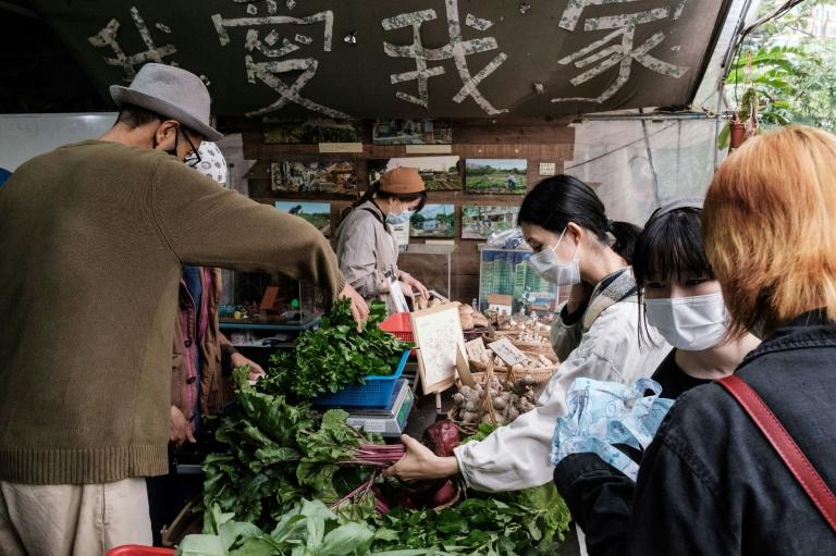 Mandy Tang (d) achète des betteraves produites localement à la ferme communautaire de Mapopo, le 18 mars 2020 à Hong Kong