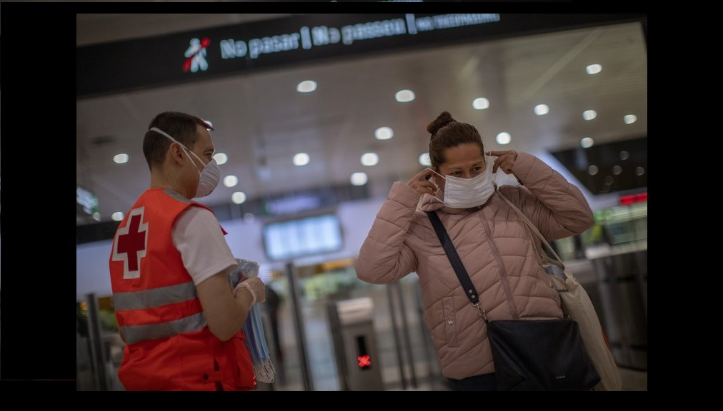 A passenger receives a face mask distributed by a red cross volunteer at the main train station in Barcelona, Spain, Tuesday, April 14, 2020. (AP Photo/Emilio Morenatti)