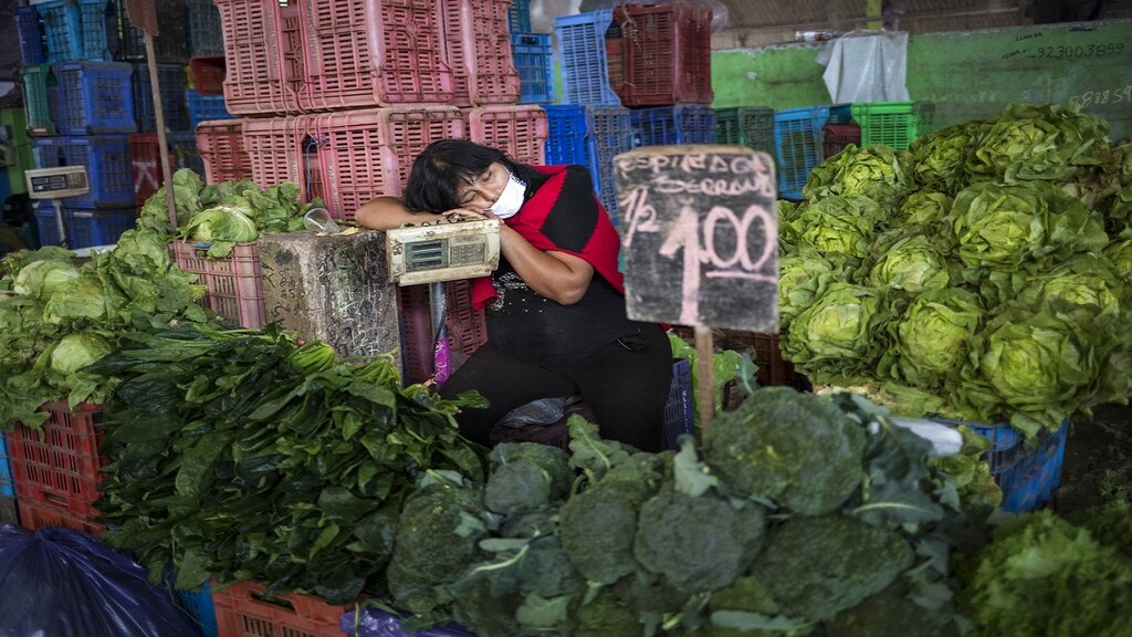 Kathy Velazquez, wearing a protective face mask as a precaution against the new coronavirus, naps in her vegetable stall as she waits for customers in Lima, Peru, Saturday, April 11, 2020. (AP Photo/Rodrigo Abd)