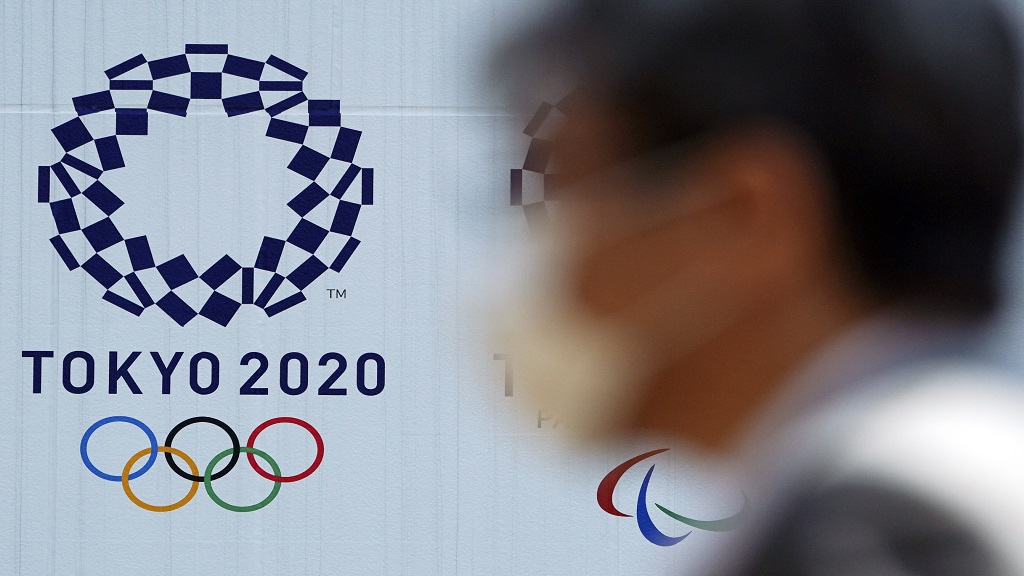 In this April 2, 2020, file photo, a man wearing a face mask walks near the logo of the Tokyo 2020 Olympics, in Tokyo. (AP Photo/Eugene Hoshiko, File).