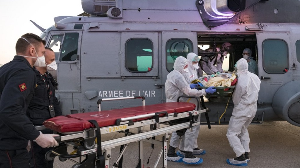 In this photo provided by the French Army Thursday, April 2, 2020, medical staffs evacuate a patient infected with the Covid-19 virus, Wednesday April 1, 2020 at Orly airport, south of Paris. The operation aims at relieving hospitals in the Paris region, hardly hit by the coronavirus. The new coronavirus causes mild or moderate symptoms for most people, but for some, especially older adults and people with existing health problems, it can cause more severe illness or death. (Julien Fechter/DICOD via AP)