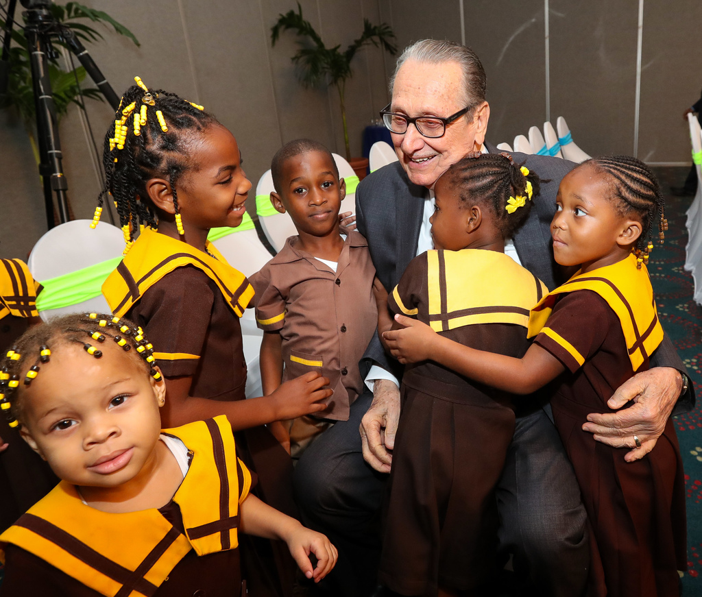 Chairman of Sagicor Foundation, R Danny Williams shares a light moment with infants, who benefited from a Sagicor Foundation programme. (File photo)
