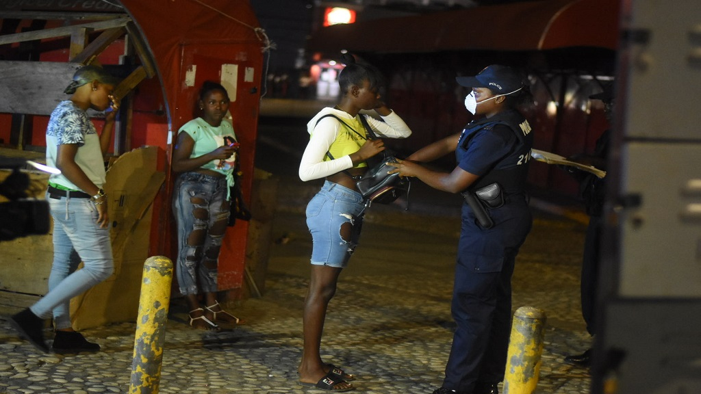 The bag of one youngster from a group who was seen in Half-Way Tree, St Andrew during the curfew hours, being searched by a policewoman on Wednesday night.
