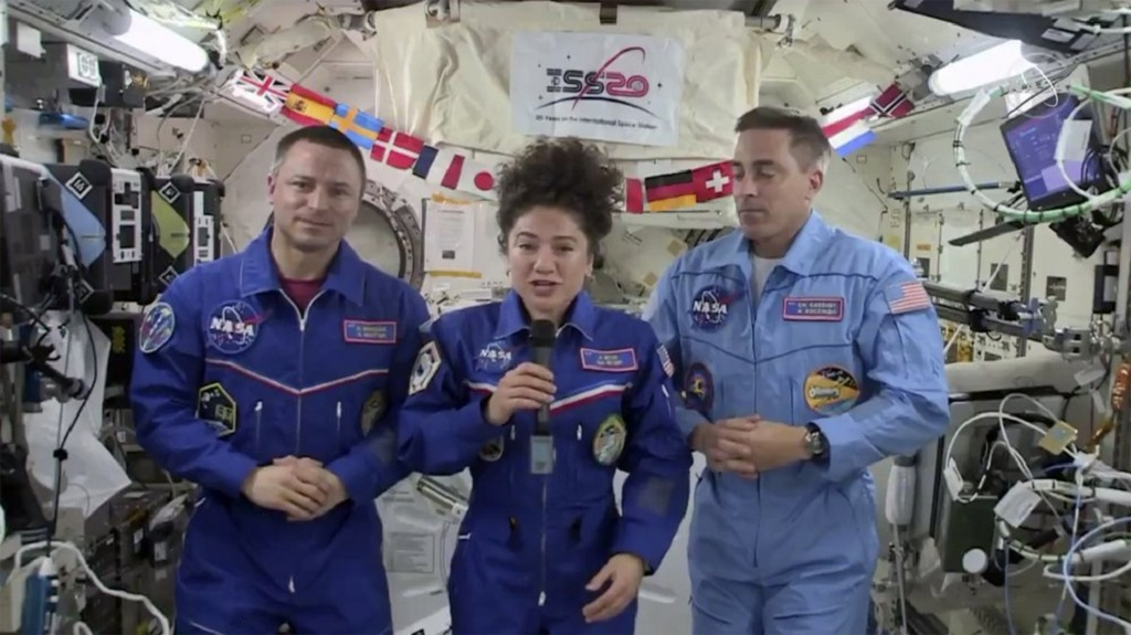 In this image from video made available by NASA, U.S. astronaut Jessica Meir speaks, accompanied by Andrew Morgan and Chris Cassidy, during a news conference held by the American members of the International Space Station on Friday, April 10, 2020. Meir and Morgan said they expect it will be tough returning to such a drastically changed world next week, after a half-year or more in space. (NASA via AP)