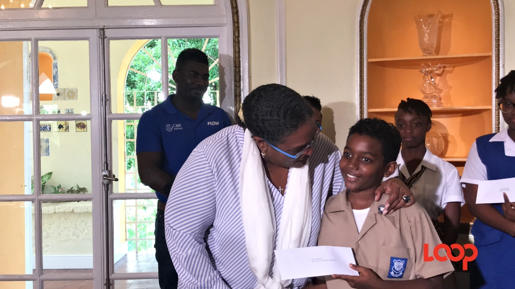 Prime Minister Mia Mottley congratulating and chatting with the overall regional first-place prize winner in the Juniors of the FCCA 2019 Children's Essay Competition, nine-year-old Noel Allder of the St. Paul's Primary School on November 21, 2019. (FILE)