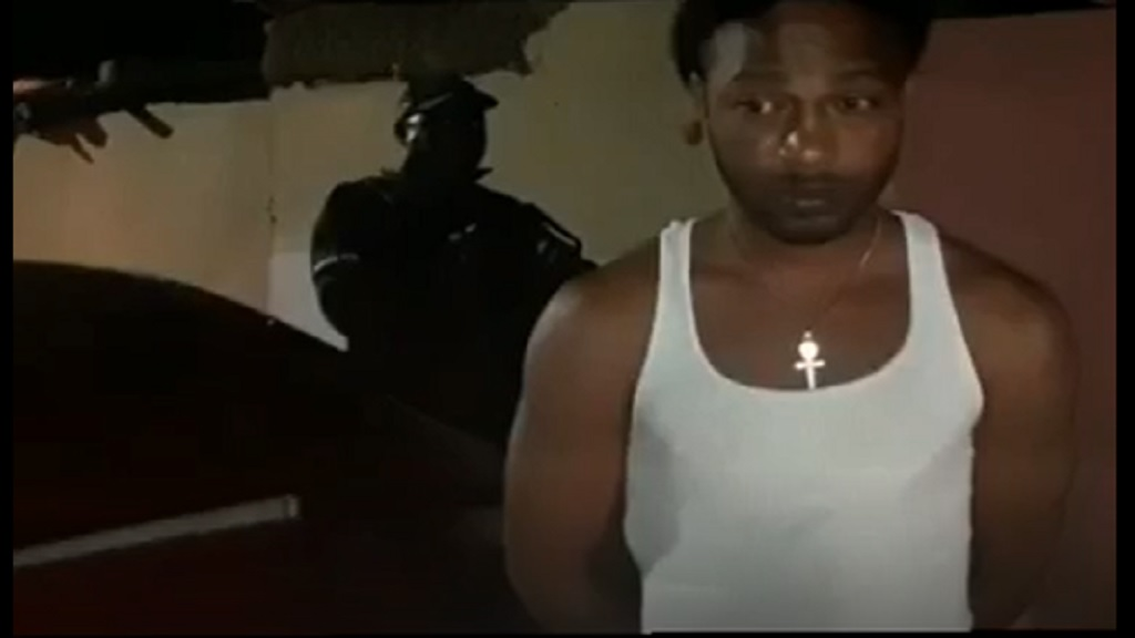 In this screengrab, Dayne Mitchell is seen in handcuffs after he was seen in a video stating his intention not to comply with the all-island curfew order.