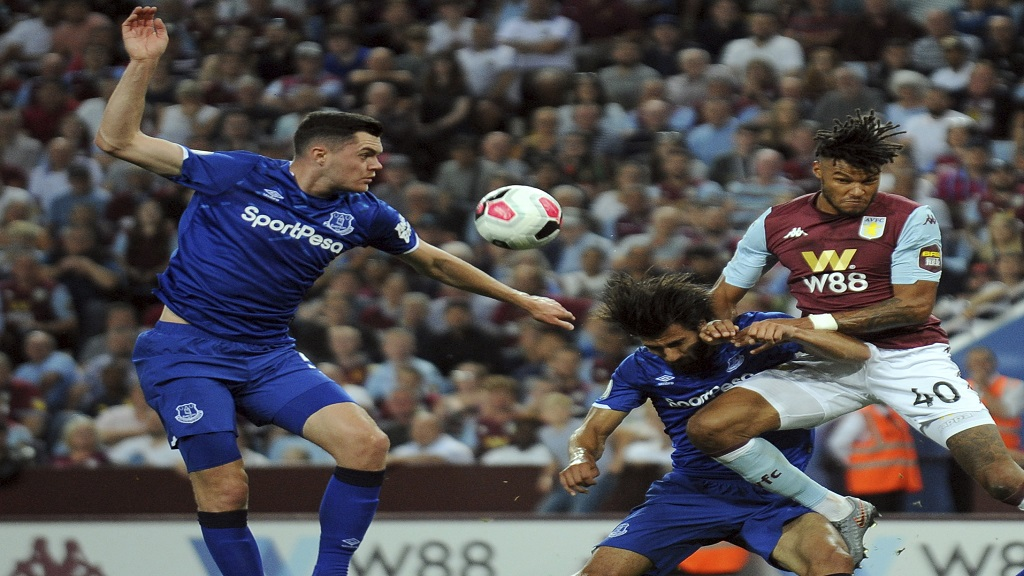 Aston Villa's Tyrone Mings, right, duels for the ball with Andre Gomes, centre and   Michael Keane of Everton during their English Premier League football match  at Villa Park in Birmingham, England, Friday, Aug. 23, 2019. (AP Photo/Rui Vieira).