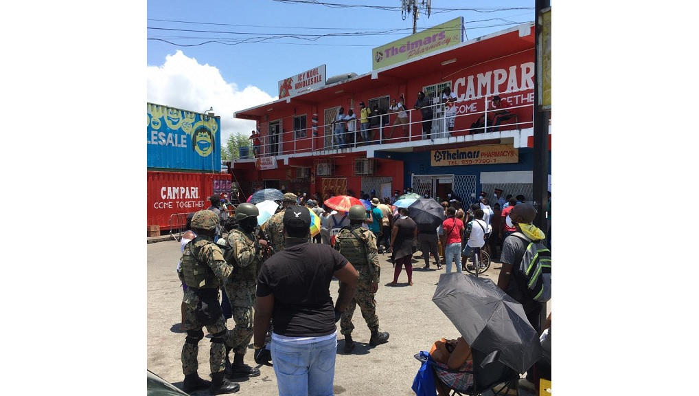 Soldiers look on at a crowd outside the Western Union outlet at Thelmar's Pharmacy on Passage Fort Drive in Portmore, St Catherine on Wednesday. (Photos: Lynford Simpson)