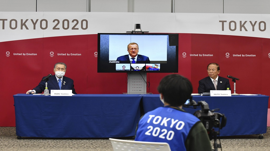 Tokyo 2020 Organising Committee President Yoshiro Mori, left, and CEO Toshiro Muto, right, attend teleconference with International Olympic Committee member John Coates, who heads the inspection team for Tokyo Olympics, in Tokyo Thursday, April 16, 2020. Tokyo Olympic organizers and the IOC said Thursday they will cut some of the extras out of next year's postponed games, an attempt to limit what is expected to be billions of dollars in added expenses.(Kazuhiro Nogi/Pool Photo via AP).