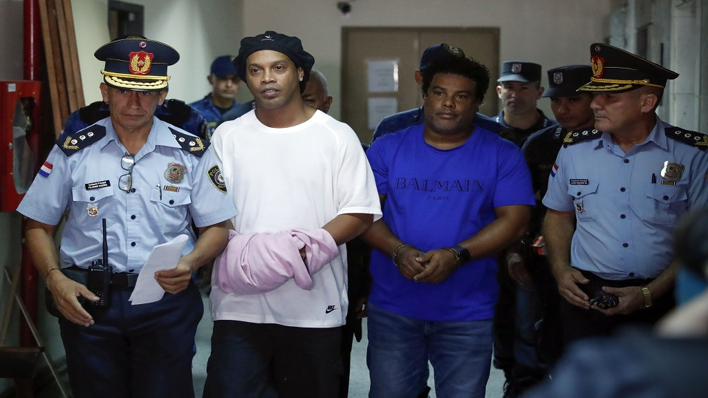 Former football star Ronaldinho, second from left, and his brother Roberto de Assis Moreira escorted by police officers to declare to judge Clara Ruiz Diaz at Justice Palace in Asuncion, Paraguay, Saturday, March 7, 2020.