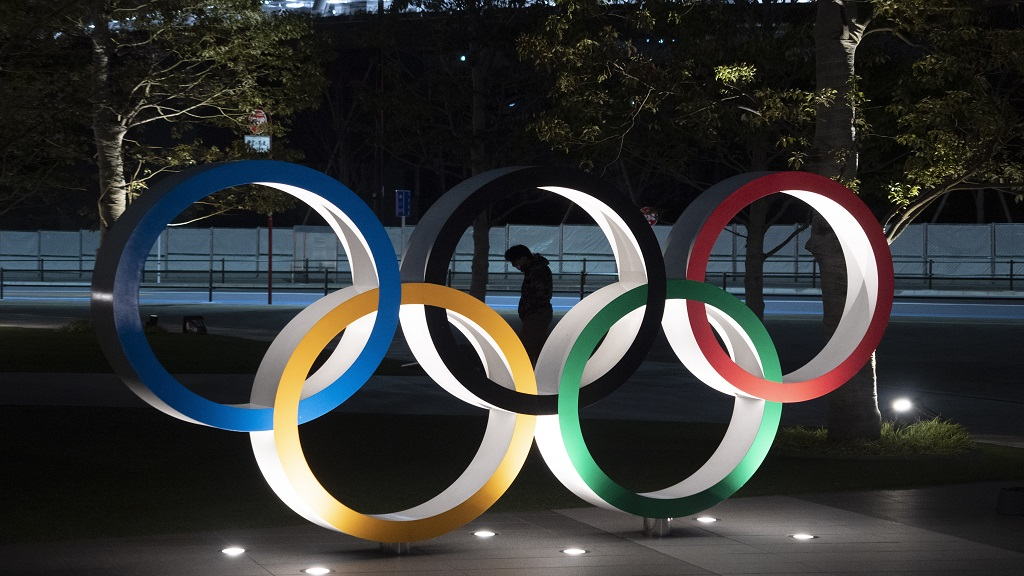 In this Tuesday, March 24, 2020 file photo, a man is seen through the Olympic rings in front of the New National Stadium in Tokyo. The Tokyo Olympics were postponed a month ago. But there are still more questions than answers about the new opening on July 23, 2021 and what form those games will take. (AP Photo/Jae C. Hong, File).