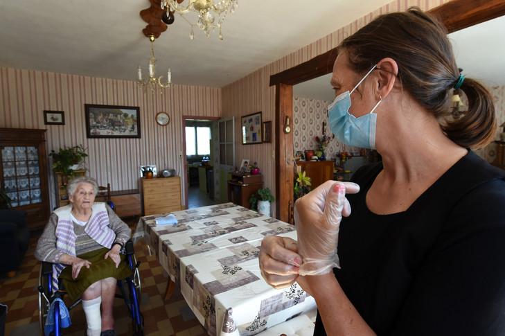 L'infirmière Diane Braccagni (g) donne ses médicaments à une patiente, Renée Bodin, 93 ans, le 27 avril 2020 à Happonvilliers / AFP