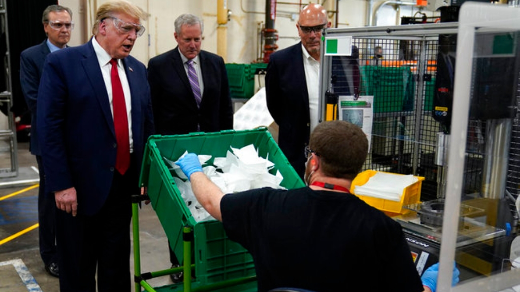 President Donald Trump participates in a tour of a Honeywell International plant that manufactures personal protective equipment, Tuesday, May 5, 2020, in Phoenix, with Tony Stallings, vice president of Integrated Supply Chain at Honeywell, right and White House chief of staff Mark Meadows. (AP Photo/Evan Vucci)