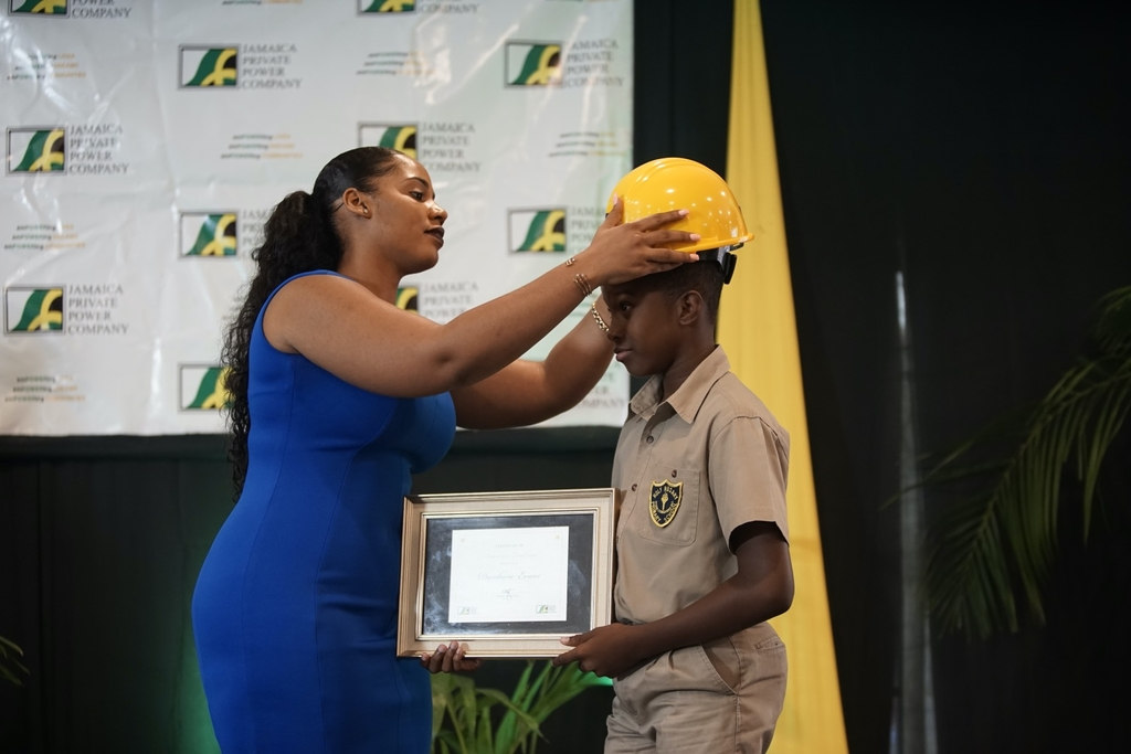 JPPC New Business Officer, Halle Salmon, places a hard hat on the head of Dushane Evans, JPPC 2019 Scholarship PEP awardee.