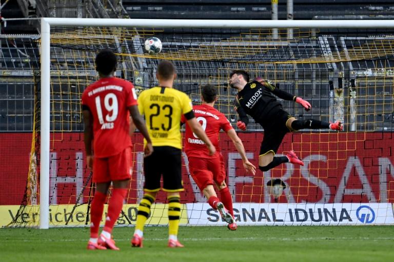 Le gardien suisse de Dortmund, Roman Buerki (d), ne parvient pas à arrêter le ballon lobé du milieu du Bayern Munich, Joshua Kimmich (pas sur la photo) lors du match de Bundesliga à Dortmund, le 26 mai 2020