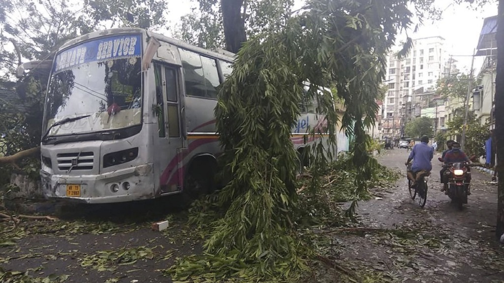 Commuters move past a tree branch precariously hanging after cyclone Amphan hit the region, in Kolkata, India, Thursday, May 21, 2020. A powerful cyclone that slammed into coastal India and Bangladesh has left damage difficult to assess Thursday. (AP Photo/Bikas Das)