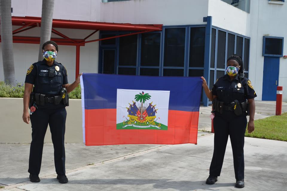 Des agents du département de police de Miami, brandissant le drapeau haïtien. Crédit photo : Page Facebook The Haitian American.