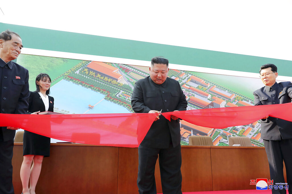 In this Friday, May 1, 2020, photo provided by the North Korean government, North Korean leader Kim Jong Un, center, cuts a tape, watched by his sister Kim Yo Jong, during his visit to a fertiliser factory in Sunchon, South Pyongan province, near Pyongyang, North Korea.
