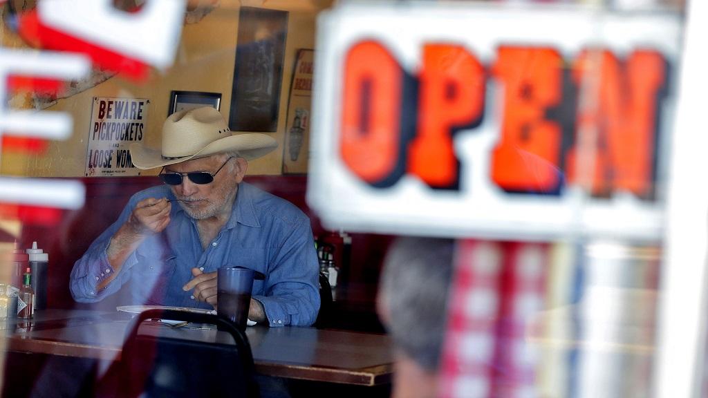 A customer eats inside the Horseshoe Cafe Friday, May 1, 2020, in Wickenburg, Arizona. (AP Photo/Matt York)