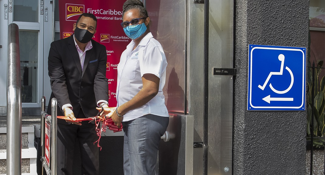Dr Christene Hendricks (r), Executive Director of the Council for Persons with Disabilities and Nigel Holness, Managing Director of CIBC FirstCaribbean International Bank, cut the ribbon commissioning the Chair lift installed by the bank at its Knutsford Boulevard, New Kingston Headquarters.