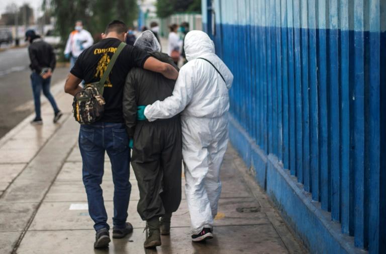 Une femme qui vient de perdre son mari, qui a succombé au Covid-19, est réconfortée par des proches, devant l'hôpital Alberto Sabogal, à Lima, au Pérou, le 27 mai 2020