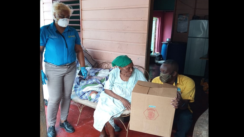 Simone Saunderson (left), assistant depot manager at JP St. Mary's Farms and Councillor for the Annotto Bay Division of the St Mary Municipal Corporation Hugh Bryan (right)delivered a care package on behalf of JP St. Mary's Farms to an elderly resident in Annotto Bay.