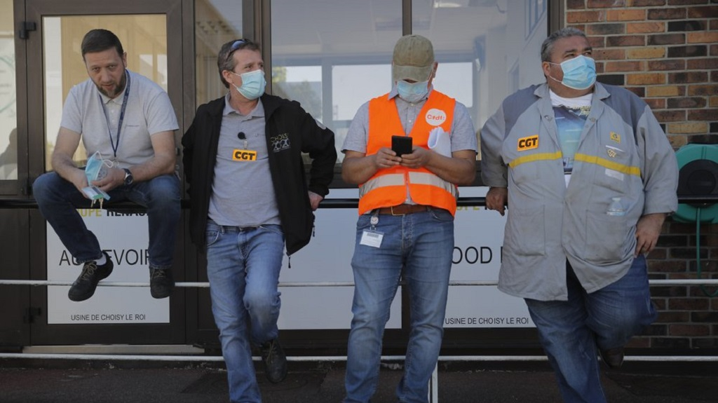 Protesting Renault workers stand outside their plant Friday, May 29, 2020 in Choisy-le-Roi, outside Paris. Struggling French carmaker Renault announced 15,000 job cuts worldwide as part of a 2 billion euros cost-cutting plan over three years. The cost-cutting plan comes as Renault came into the virus crisis in particularly bad shape. Its alliance with Nissan and Mitsubishi is a major global auto player but has struggled since the 2018 arrest of its longtime star CEO Carlos Ghosn. (AP Photo/Christophe Ena)