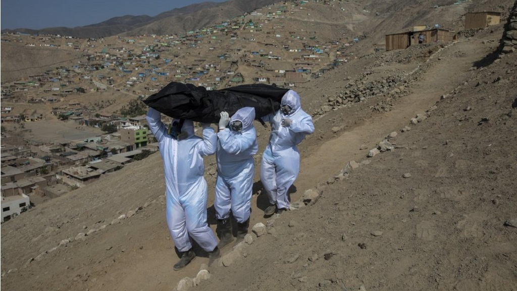 Venezuelans Luis Zerpa, from left, Luis Brito and Jhoan Faneite, carry a body bag that contains the remains of 51-year-old Marcos Espinoza who is suspected to have died of the COVID-19, down a steep hill to a waiting hearse in a working-class neighborhood near Pachacamac, the site of an Inca temple, on the outskirts of Lima, Peru, Friday, May 8, 2020. (AP Photo/Rodrigo Abd)
