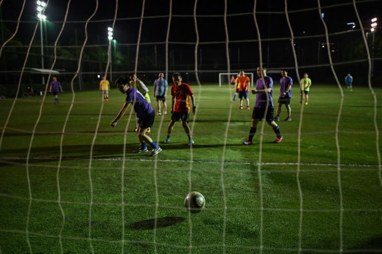 Des amateurs de football pratiquent leur sport sur un terrain de Wuhan en Chine le 19 mai 2020. La ville était au coeur de la pandémie mondiale de coronavirus, mais la levée du strict confinement fin avril a permis aux amateurs de re chausser leurs crampons. (Archives)