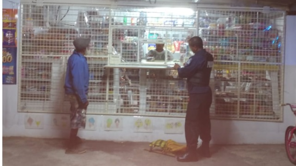Warned: A mini-mart owner is spoken to by a police officer regarding the 6pm closing time stipulated for his business.