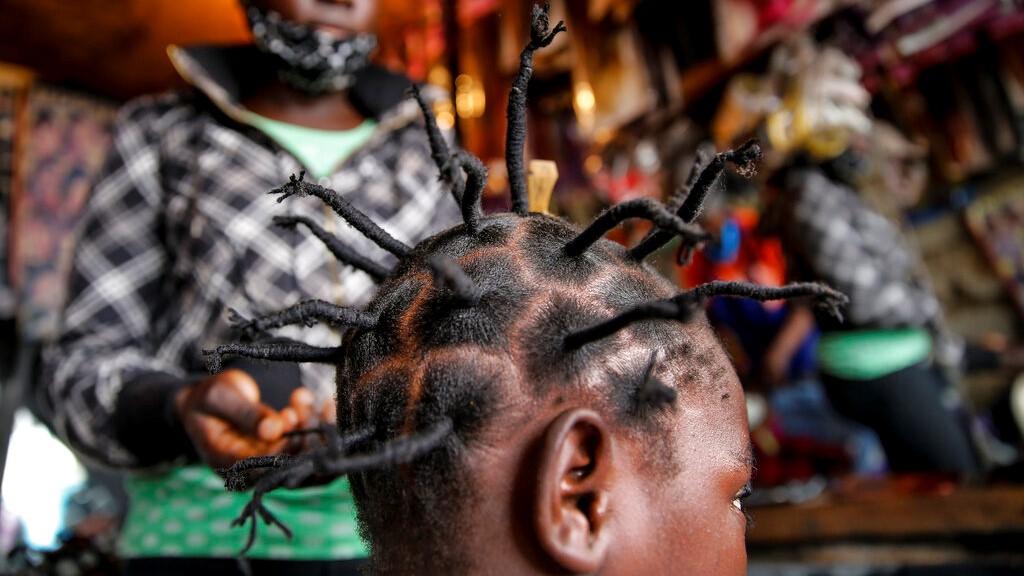 Dans cette photo d'archive du dimanche 3 mai 2020, Gettrueth Ambio, 12 ans, se fait coiffer sous la forme du nouveau coronavirus, au salon de beauté Mama Brayo dans le bidonville de Kibera de Nairobi, au Kenya. (Photo AP / Brian Inganga, dossier)