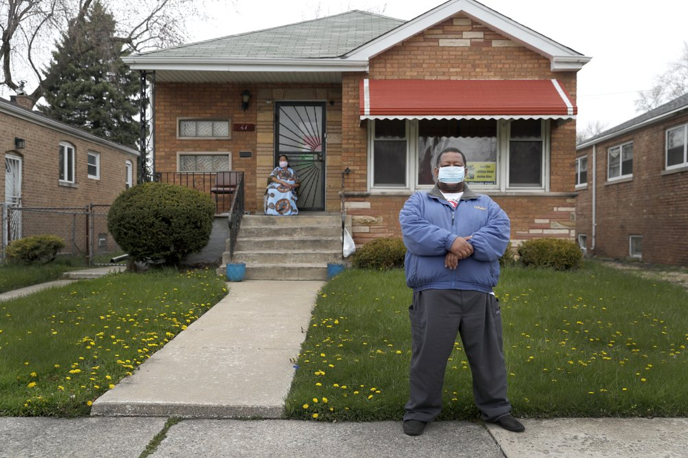 Anthony Travis, who has recovered from COVID-19 and lives with his sister, Jacqueline K Johnson (background) and an adult daughter, poses for a portrait outside his Riverdale, Illinois, home in April. (AP Photo/Charles Rex Arbogast)