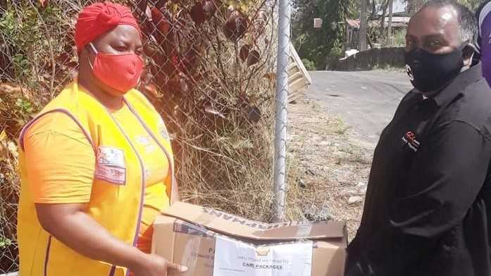 sa Atwater, Moruga teacher and member of the San Fernando Lions Club with a staff member from Allied Caterers carry one of the care packages to be delivered in the communities