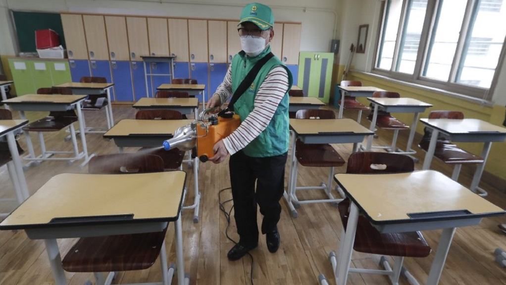 A worker wearing a face mask disinfects as a precaution against the new coronavirus ahead of school reopening in a class at Yeouido Girls High School in Seoul, South Korea, Tuesday, May 19, 2020. South Korean Vice Health Minister Kim Gang-lip urged vigilance to maintain hard-won gains against the virus and called for education officials to double check preventive measures with high-school seniors returning to school on Wednesday. (AP Photo/Ahn Young-joon)