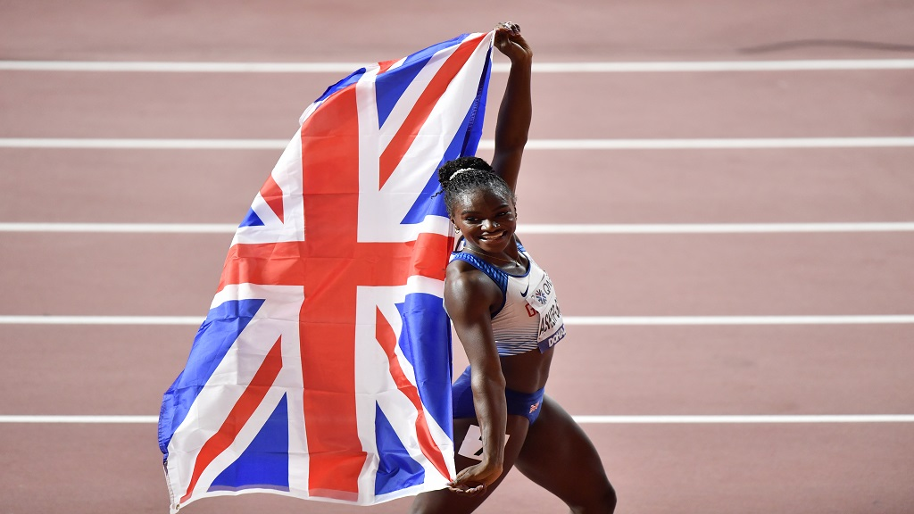 Gold medallist Dina Asher-Smith, of Great Britain, celebrates with the Union flag after winning the women's 200m final at the World Athletics Championships in Doha, Qatar, Wednesday, Oct. 2, 2019. (AP Photo/Martin Meissner).