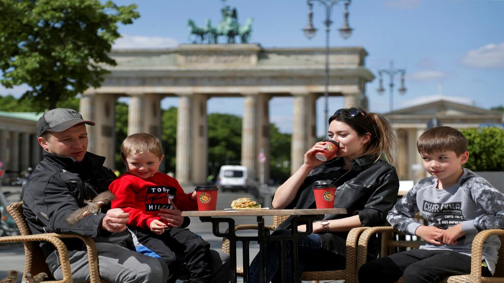 From left, Tejmur, Naile, Layla and Emil Hacimuradov from Neuwied enjoy to feed sparrows as they have breakfast in a bakery at the Brandenburg Gate in Berlin, Germany, Friday, May 15, 2020. After month of a nationwide lockdown restaurants are reopening in more German states on Friday. (AP Photo/Michael Sohn)