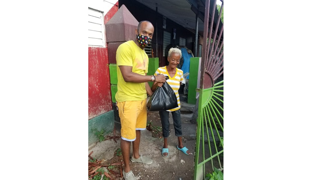 Tommica Foreman from Kirk and Frame Production donates a care package to an elderly resident of Grants Pen in St Andrew.