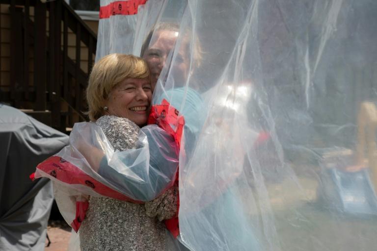 """Carolyn Ellis serre sa mère dans ses bras grâce à un """"gant à câlin"""" qu'elle a mis au point avec son mari Andrew, le 16 mai 2020 à Guelph, dans l'Ontario"""