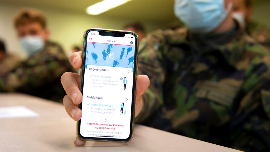 A soldier of the Swiss army wearing a protective face mask holds a smartphone with an app using Decentralized Privacy-Preserving Proximity Tracing (DP-3T) during a test with 100 soldiers in the military compound of Chamblon near Yverdon-les-Bains, Switzerland, Thursday, April 30, 2020. (Laurent Gillieron/Keystone via AP)