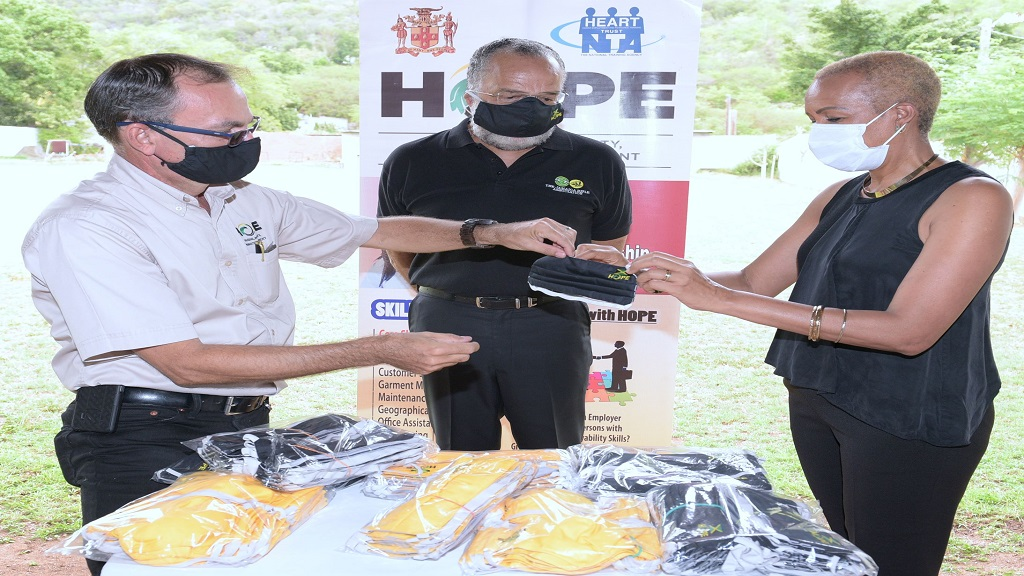 Lieutenant Colonel Martin Rickman, (left), National Coordinator for the Housing, Opportunities, Production and Employment (HOPE) Programme, watches as Minister of Science, Energy and Technology, Fayval Williams, (right) inspects one of the reusable face masks made by the progamme's participants while president of the Jamaica Rifle Association (JRA), Major John Nelson looks on during a presentation ceremony at  the JRA range on Thursday May 14, 2020.