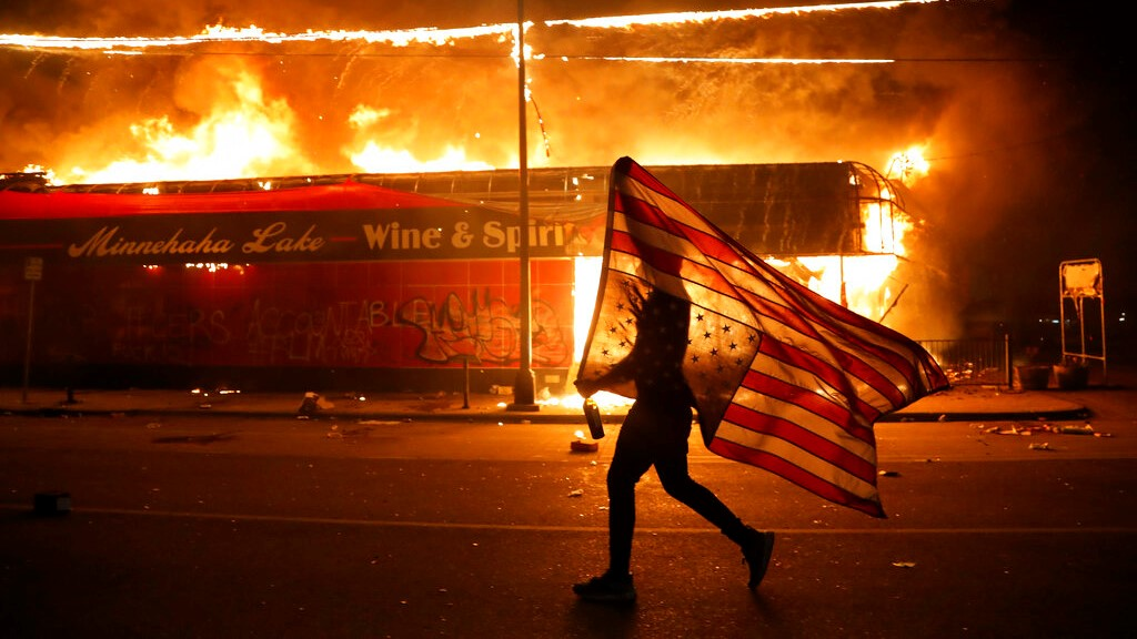 A protester carries a US flag upside down, a sign of distress, next to a burning building Thursday, May 28, 2020, in Minneapolis. (AP Photo/Julio Cortez)