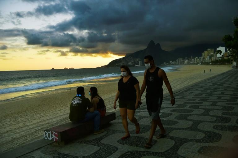 Promeneurs portant des masques sur la plage d'Ipanema à Rio de Janeiro, le 19 mai 2020