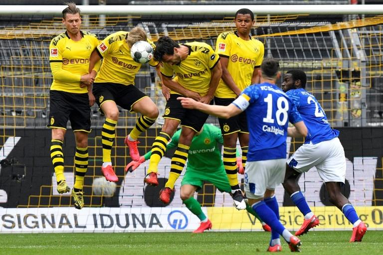 Coup franc du milieu de Schalke 04, Daniel Caligiuri (18), arrêté par les joueurs du Borussia Dortmund lors du premier match de reprise de la Bundesliga, à Dortmund, le 16 mai 2020
