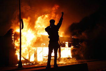 In this May 29, 2020, photo, a check-cashing business burns during protests in Minneapolis. Protests continued following the death of George Floyd, who died after being restrained by Minneapolis police officers on Memorial Day. (AP Photo/John Minchillo)